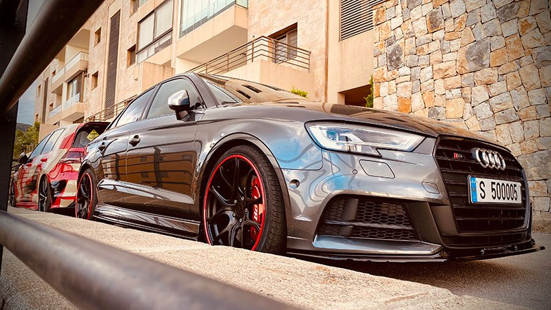 Audi with red AlloyGator wheel protection parked against a curb